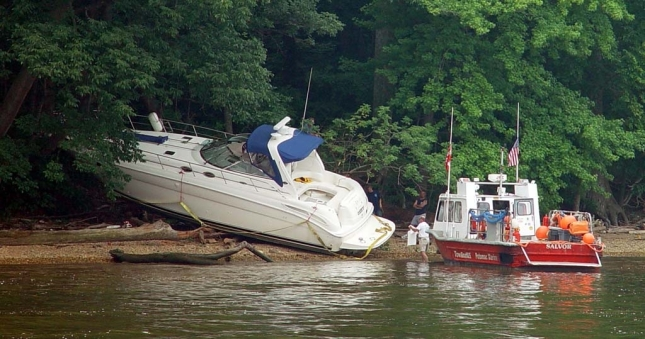 Is this a towing job or a salvage job? Boats that are hard aground like this cruiser are most likely to be declared salvage, which is not typically covered by a towing service plan, says BoatUS.