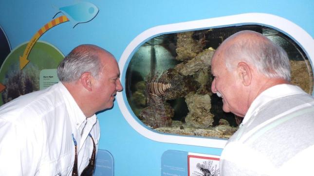 U.S. Congressman Steve Southerland (left), of Panama City, Fla., and Capt. Bill Kelly, Exec. Dir. of the Florida Keys Commercial Fisherman's Association, view a lionfish on display in an aquarium at the Florida Keys National Marine Sanctuary's Eco-Discovery Center in Key West, Fla. Two rapidly reproducing and voracious non-native lionfish species, imported from the Indo-Pacific region, are wreaking havoc on fisheries and marine ecosystems in the Gulf of Mexico, Western Atlantic and the Caribbean Sea. (Photo courtesy of Melissa Thompson)